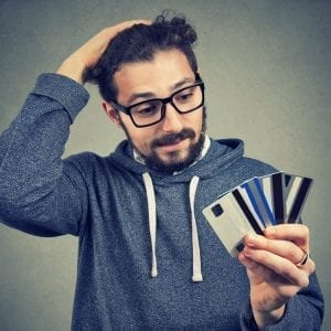 Young male student with glasses holding multiple credit cards looking stressed about his climbing debt