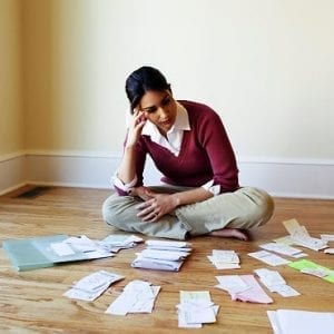 Woman looking at bills on the floor