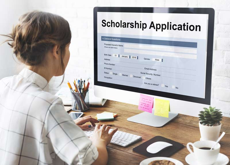 Women applying for College Scholarship and Grants on computer
