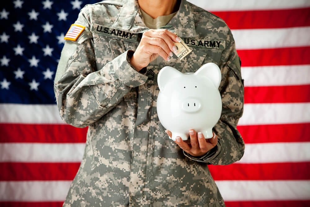Soldier holding managing finances by putting money in a piggy bank