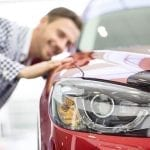 Young male student who is looking at a car to buy with a student loan