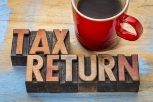 File Tax Return with cup of coffee