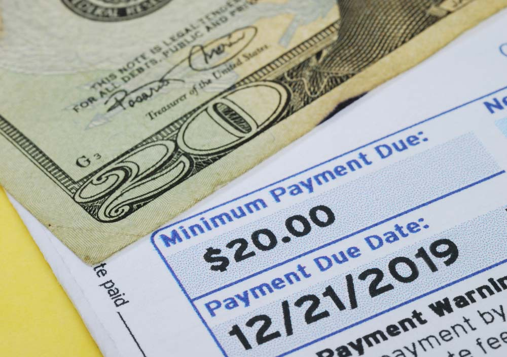 Bill to pay the minimum payment on credit card debt on table with money