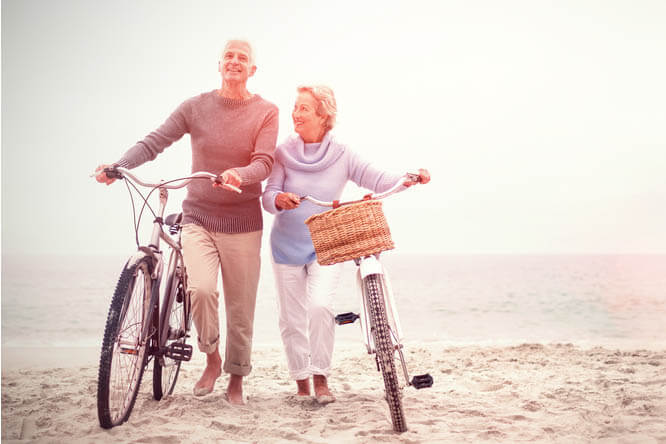Senior citizens with bikes on the beach