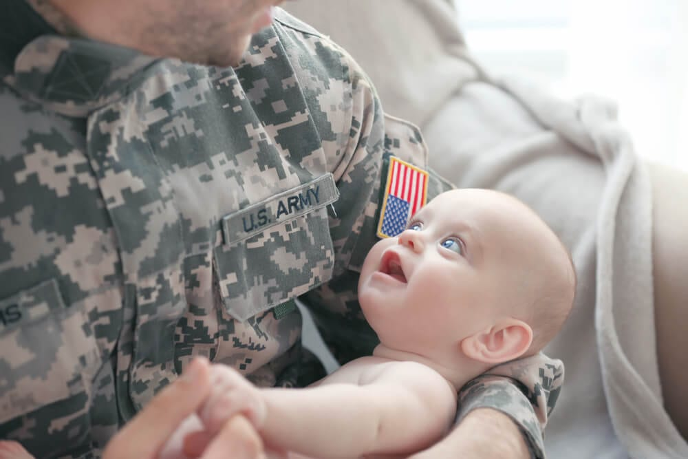 Military father holding his new born baby