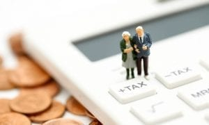 "Small model of elderly couple on calculator button that says ""tax"""