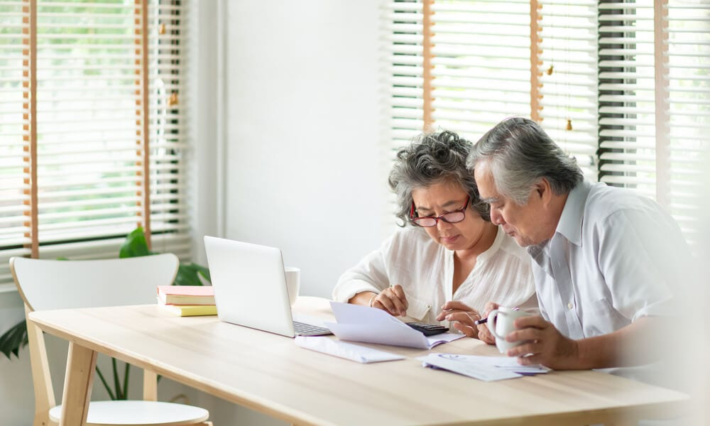 Stressed senior Asian couple looking over papers, calculator and laptop to pay bills