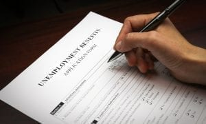 Persons hand holding pen, ready to fill out unemployment benefits form