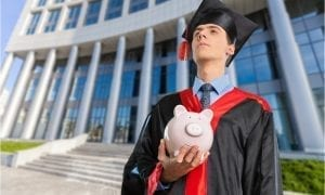 Young male student gazing into distance holding piggy-bank in front of university building