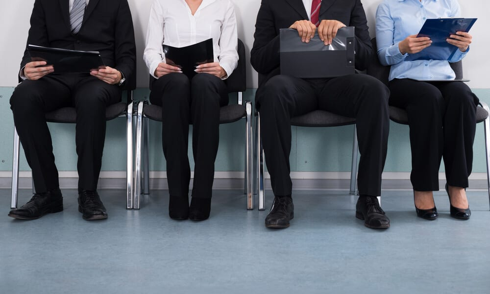Photo of business people sitting in lobby with files in hand waiting for interview