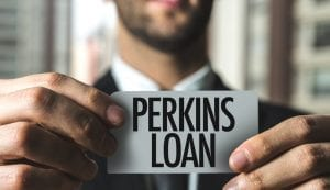 "Businessman holding in focus card that says ""Perkins Loan"" with both hands with out of focus skyscraper window in background"