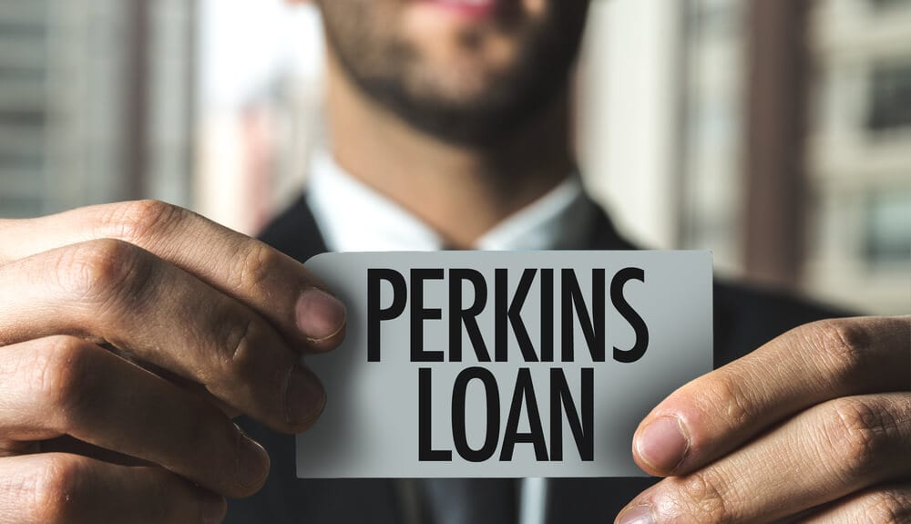 """Businessman holding in focus card that says """"Perkins Loan"""" with both hands with out of focus skyscraper window in background"""