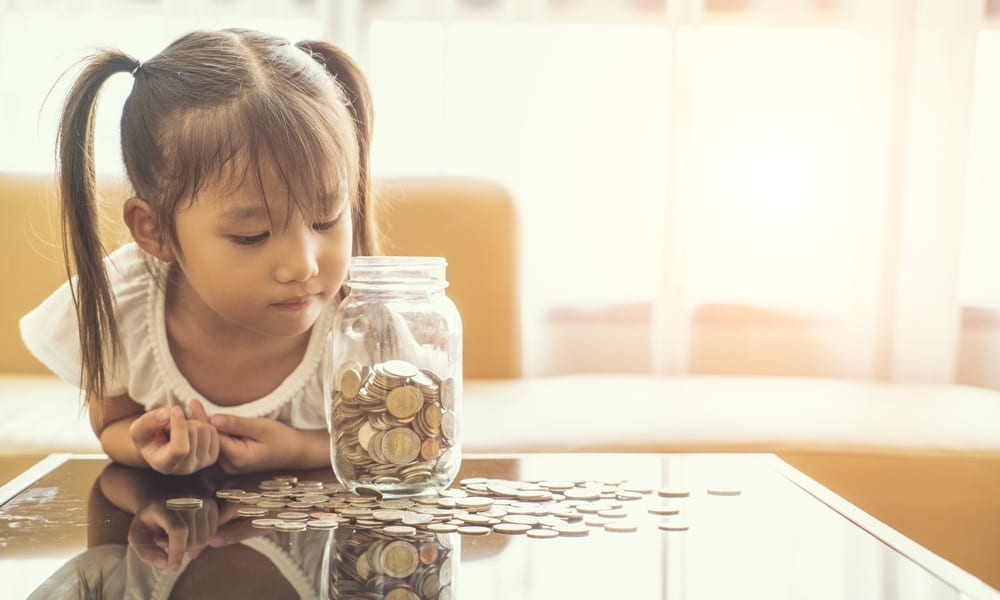 Young girl leaning on table looking over scattered coins and a jar of coins