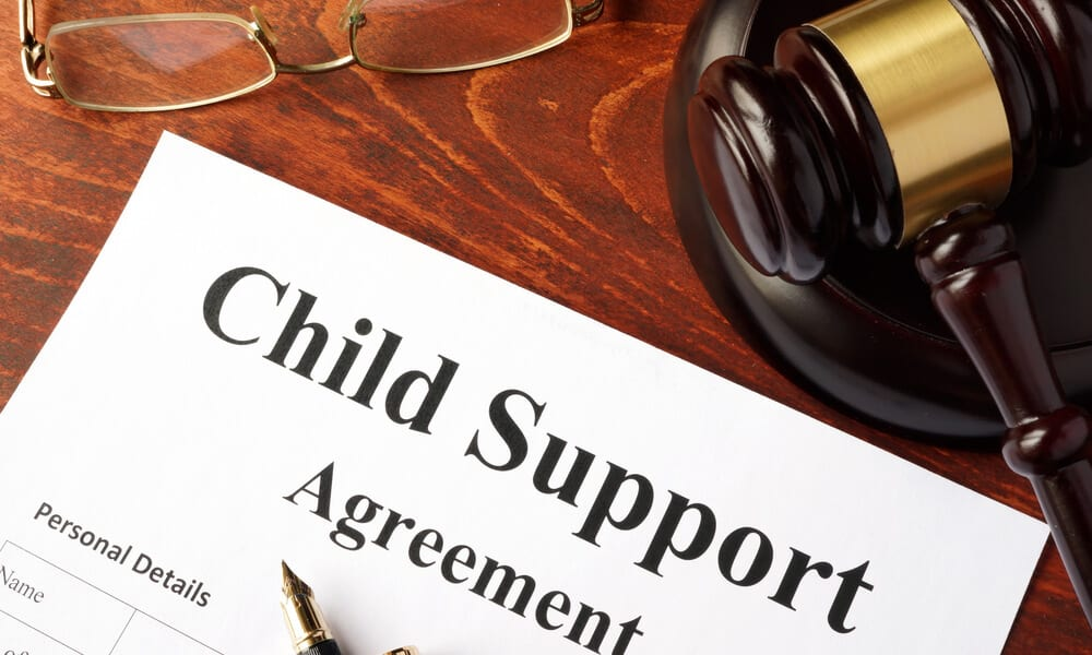 Child support agreement form on judges desk next to glasses and gavel