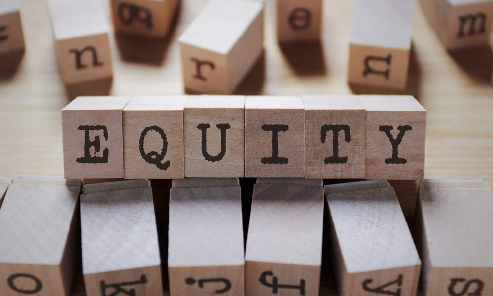 """the word """"equity"""" spelled out with toy wooden blocks on table"""