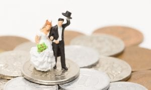 Photo of model bride and groom arm in arm walking on pile of change with groom tipping his hat
