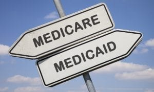 Two white direction signs with arrows and the words medicare and medicaid