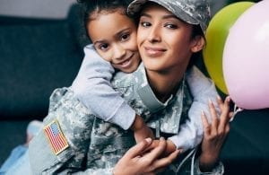 African american daughter hugging her mother in military uniform with balloons