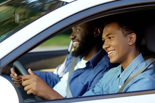 Teenager driving a car with his dad
